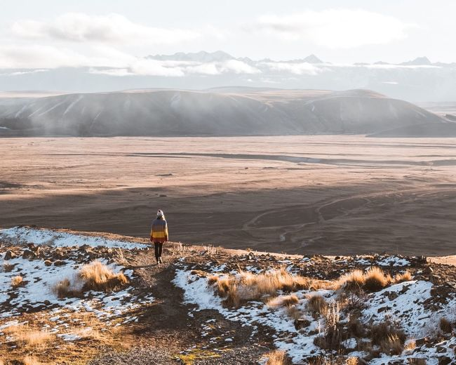 Rear view of woman walking on landscape against sky during winter