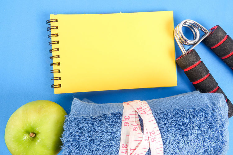 Directly above view of exercise equipment and apple on blue background