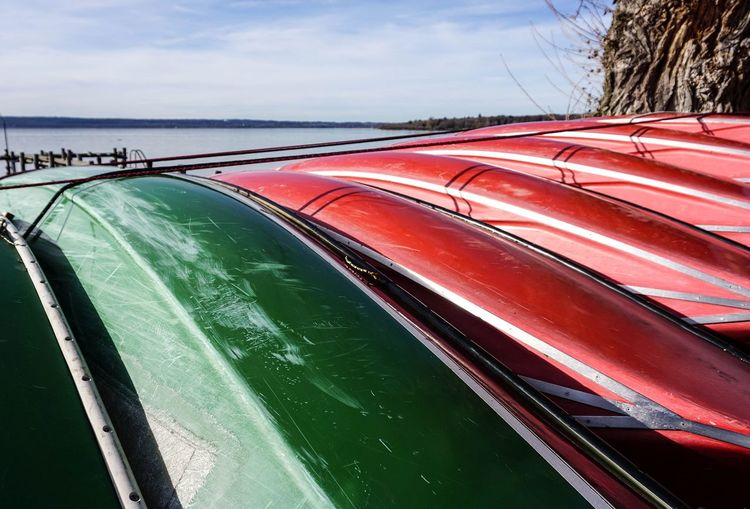 Close-up of tied canoes at beach