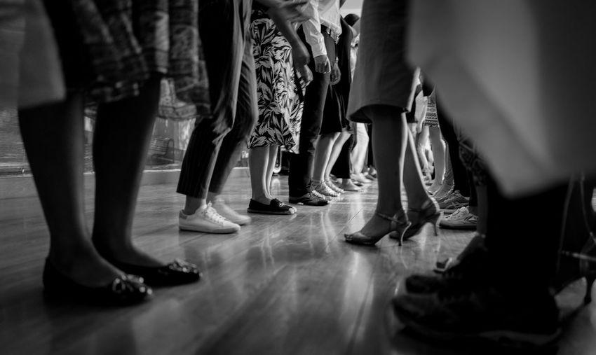 Low Section Of Men And Women Standing On Floor