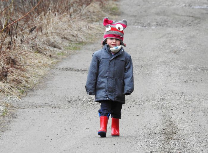 Portrait of smiling girl crying while standing on road during winter