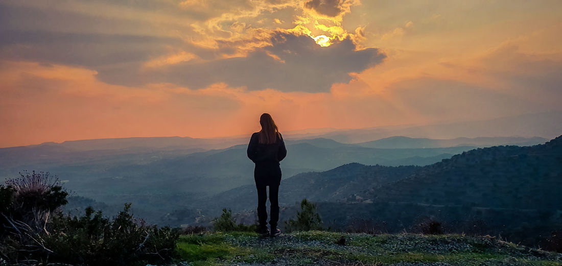 Rear view of man standing on mountain during sunset