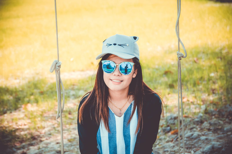 Portrait of smiling young woman sitting on swing on land