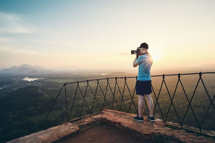 Man photographing landscape against sky during sunset