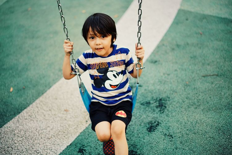 High angle view of girl on swing at playground