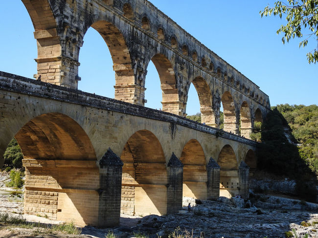 Pont-Du-Gard Ancient Ancient Civilization Arch Archaeology Architectural Column Architecture Bridge - Man Made Structure Built Structure Clear Sky Connection Day History Low Angle View Nature No People Old Ruin Outdoors Sky Sunlight Travel Travel Destinations