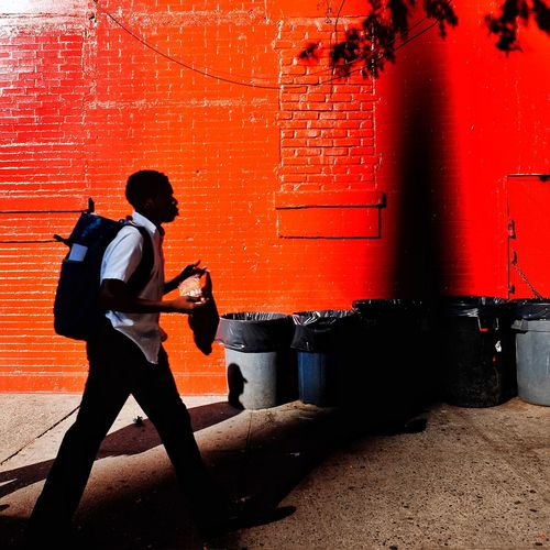 Side view of man walking against red wall