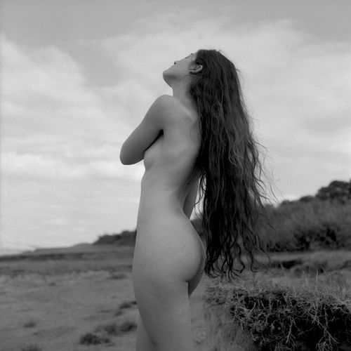 Midsection of woman standing on land against sky