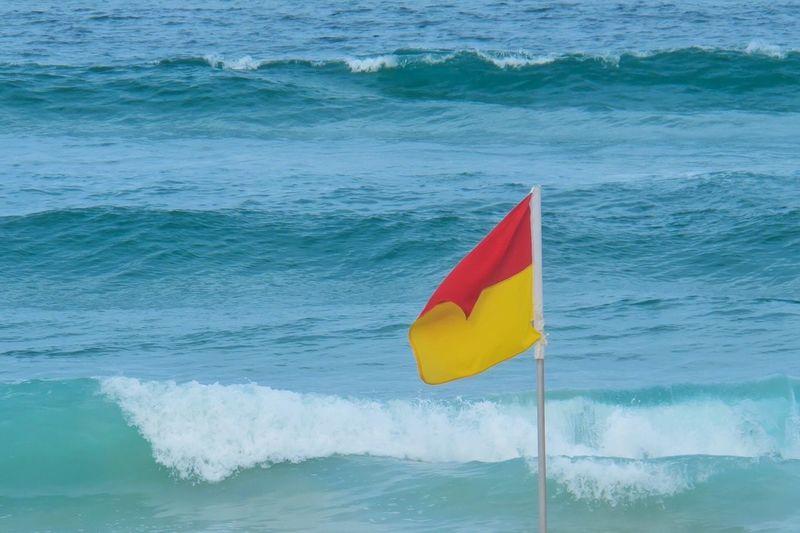 Flag against calm blue sea
