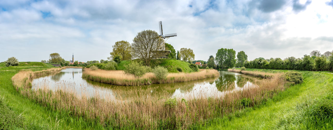 On the edge of town. Panorama Panoramic Tower Windmill Netherlands Nederland Europe Zeeland  Plant Sky Water Grass Tree Cloud - Sky Landscape Nature Environment Scenics - Nature Field Growth Tranquil Scene Tranquility Rural Scene Green Color Beauty In Nature Day Land No People Outdoors Canal Wide Nature Green Cloudscape Beautiful EyeEm Best Shots City Town Historic Tourism Tourist Destination Travel Travel Destinations