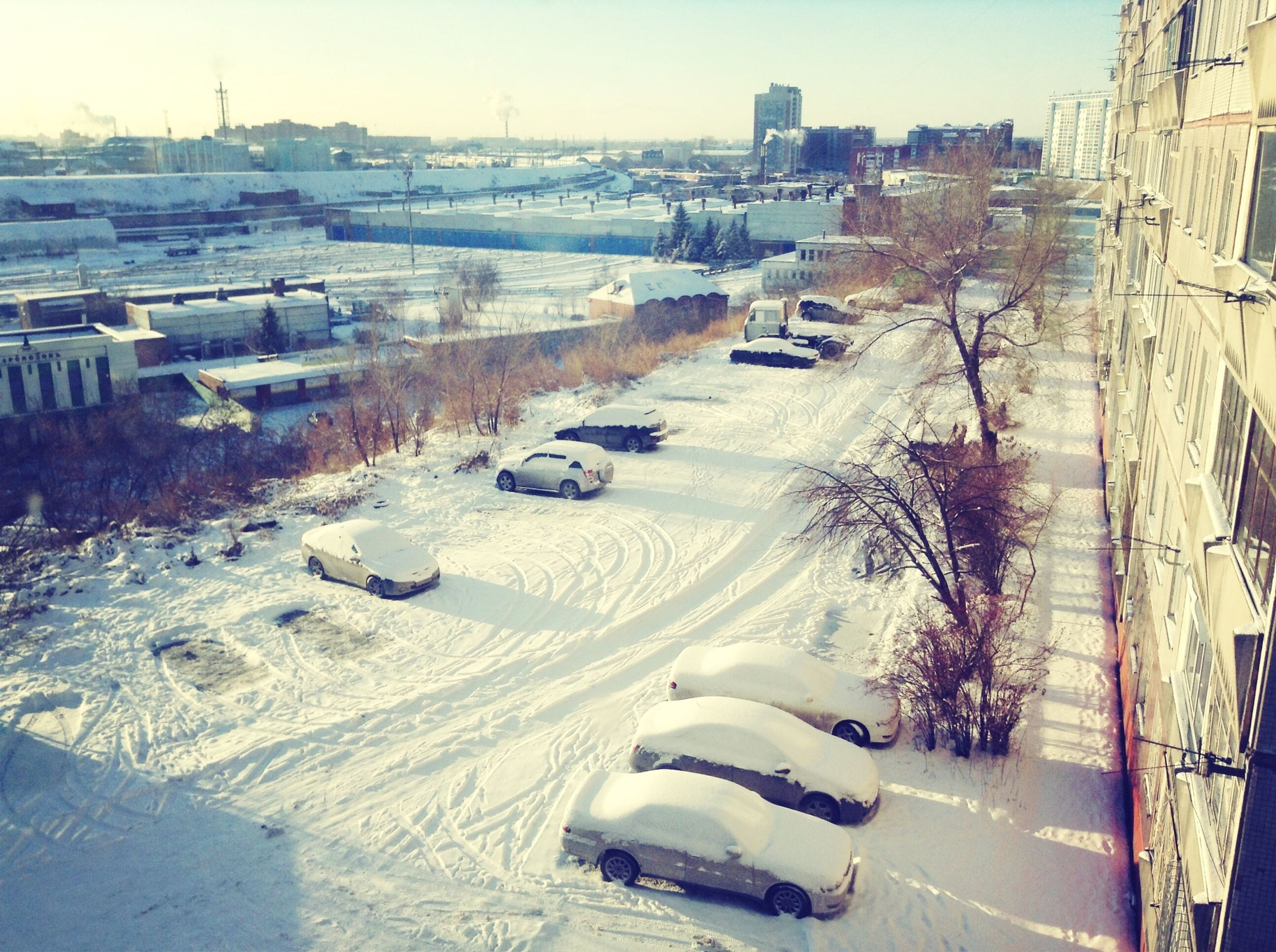 transportation, snow, building exterior, winter, cold temperature, car, architecture, built structure, street, mode of transport, road, land vehicle, high angle view, city, season, tree, sunlight, covering, outdoors, weather