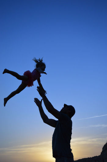 Low angle view of silhouette man catching daughter against blue sky during sunset
