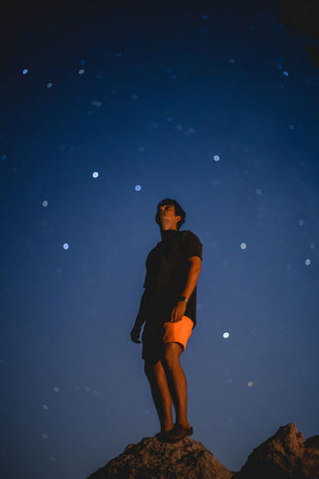 Low angle view of young man standing on rock under stars