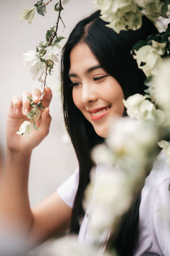 Portrait of a smiling young woman holding flowering plants