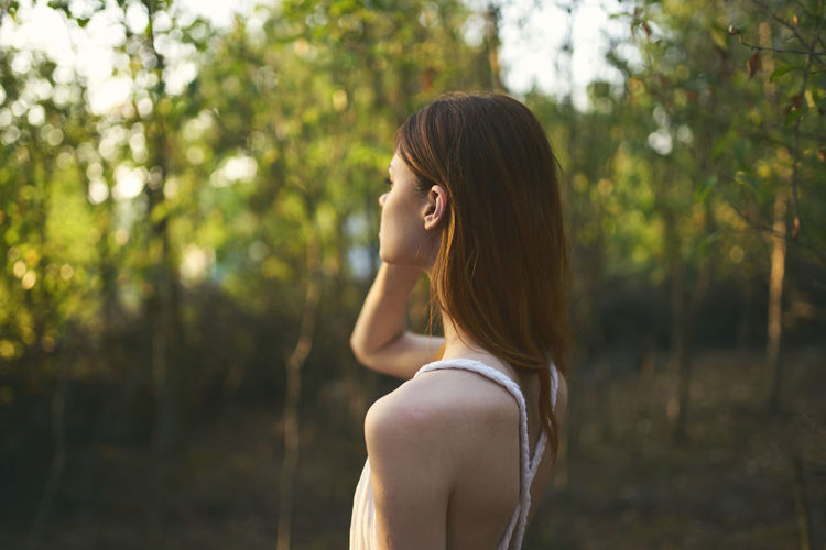 Side view of a young woman against trees