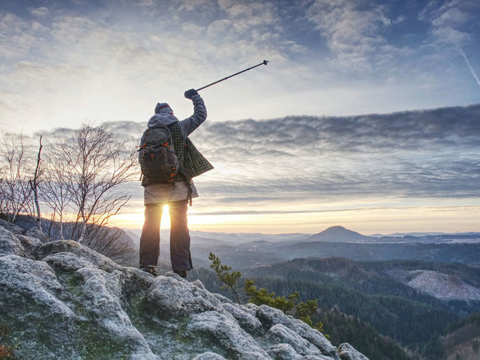 Woman reached mount peak. girl wearing backpack and using trekking sticks, enjoying daybreak