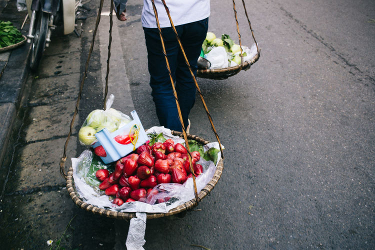 Low section of man holding fruits in basket
