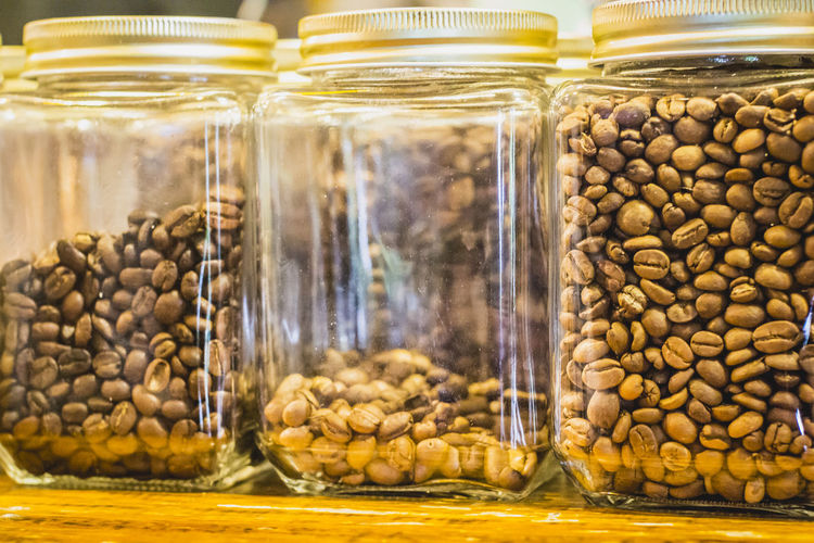 Close-Up Of Coffee Beans In Glass Containers On Table