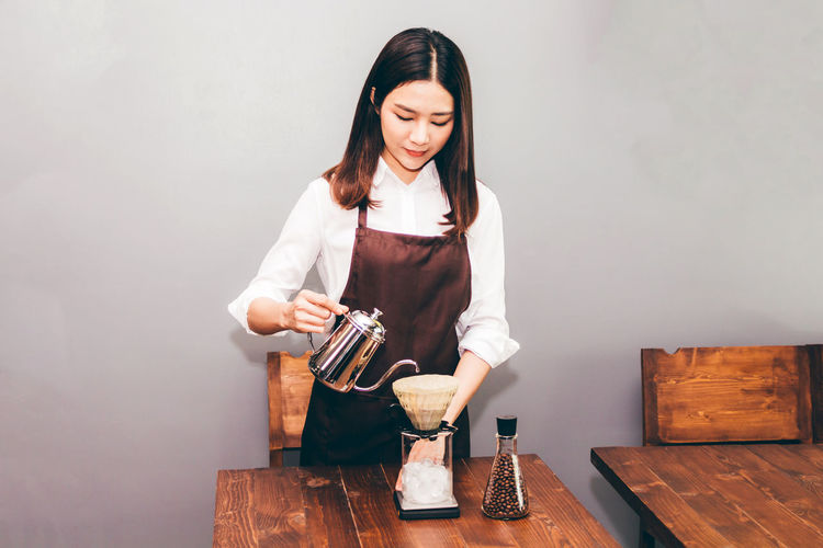 Young woman pouring coffee in filter on table against wall
