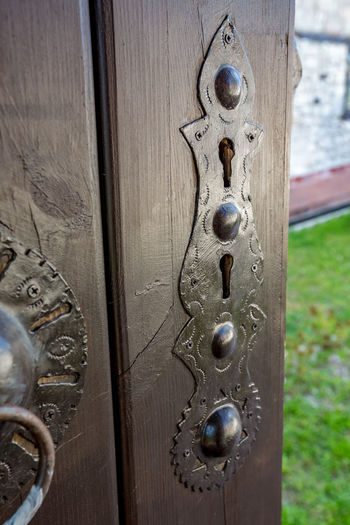 Wooden plank door with metallic double key hole escutcheon, brown painted, having nice ornamental decorations. Blurred springtime backyard. Bulgaria, village in Rhodope mountain Rhodope Mountains Rhodopes Bulgaria Carving Close-up Closed Day Door Door Knocker Doorknob Entrance Handle Keyhole Knob Lock Metal No People Old Outdoors Pattern Protection Rhodopemountains Safety Security Wood - Material