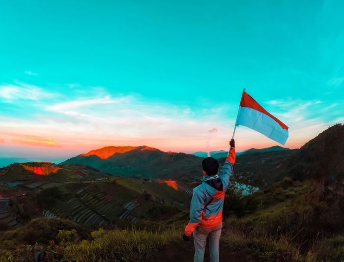 Rear View Of Man Holding Indonesian Flag While Standing On Mountain Against Sky