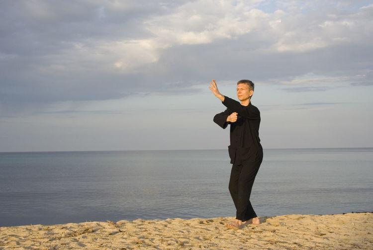 Mature man practicing tai chi at beach against sky
