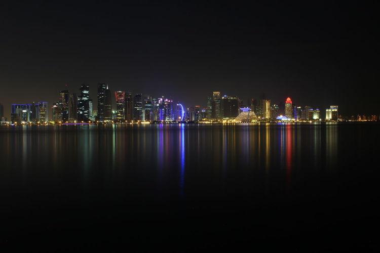 Illuminated Cityscape By River At Night