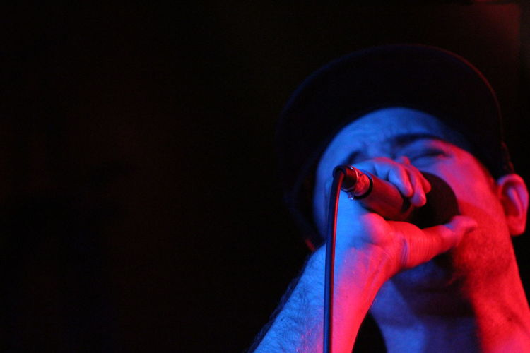Low angle view of man singing against black background