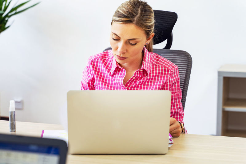 Mid adult woman using mobile phone while sitting on table