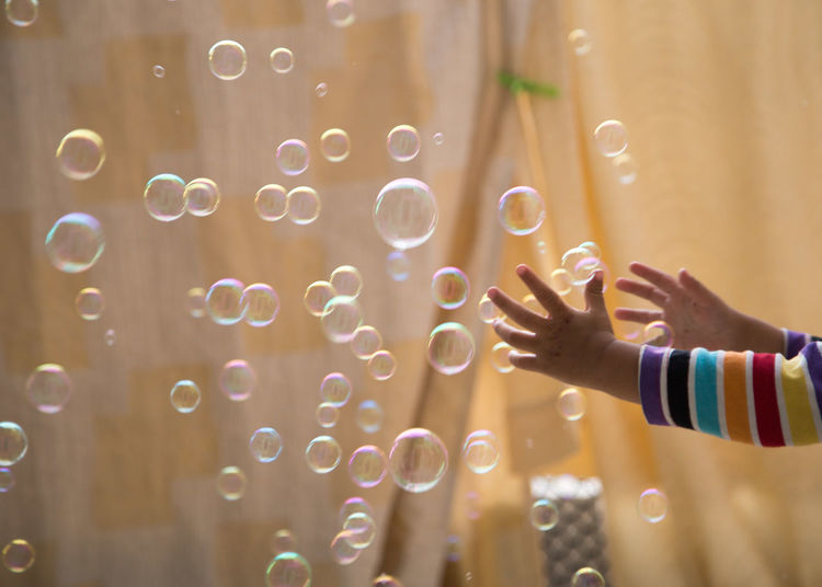 Cropped hands of child by bubbles