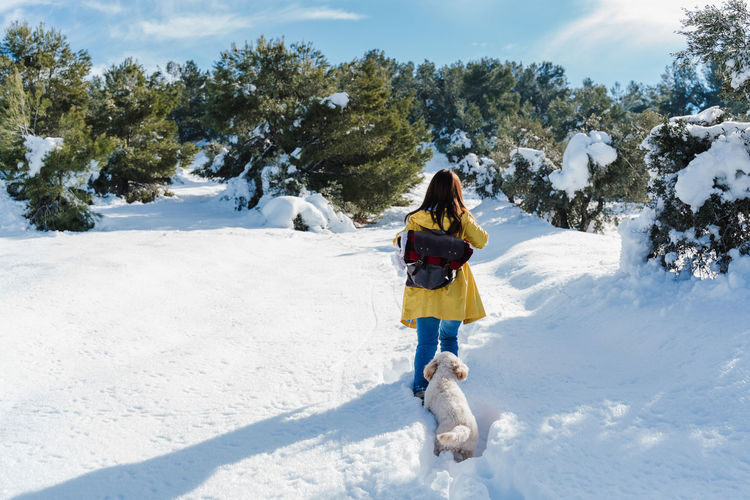 Rear view of woman on snowcapped landscape against sky