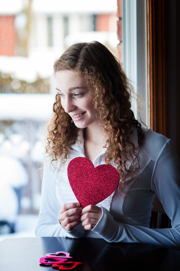 Young woman with cutout heart