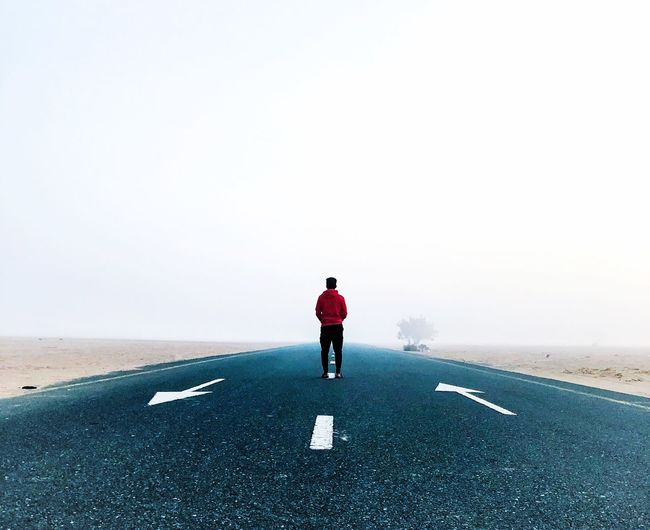 Rear view of man standing on desert road