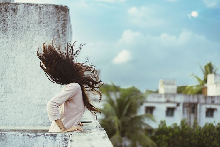 Young woman tossing hair on terrace