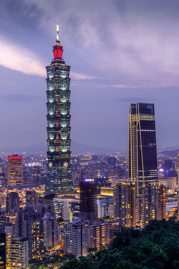Illuminated taipei 101 in city against cloudy sky