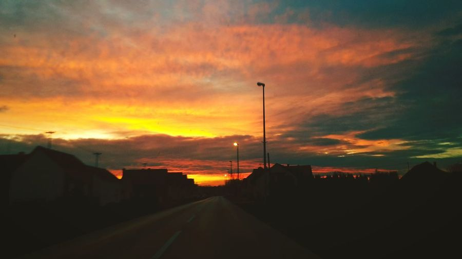 Catching Sunset while driving Sunset Electricity Pylon Tree Technology Telephone Line Road Dramatic Sky Orange Color Sky Cloud - Sky Power Line  Electric Pole Power Supply Atmospheric Mood
