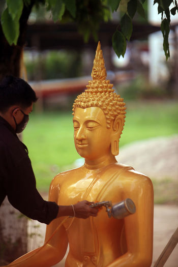 Close-Up Of Man Painting Lord Buddha Statue