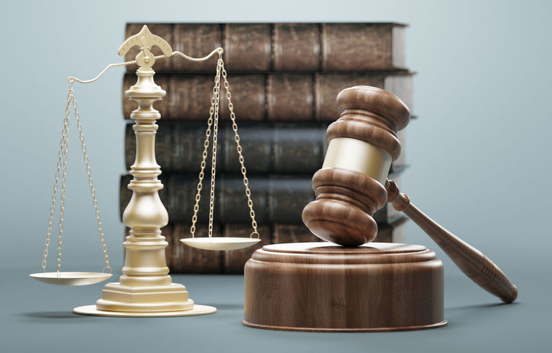 Close-Up Of Wooden Gavel By Weight Scale And Books Against Blue Background