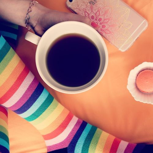 Low section of woman holding black coffee by table