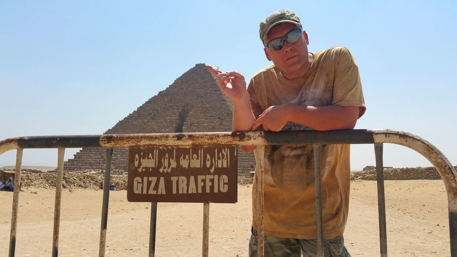 Man leaning on fence against giza pyramids