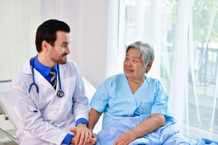 Smiling Doctor Sitting By Senior Woman In Hospital