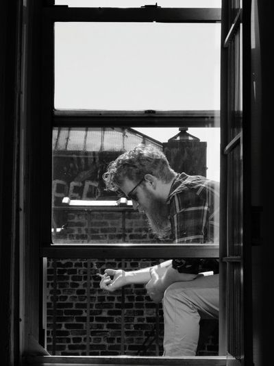 Side View Of Lumbersexual Man Smoking Cigarette By Window