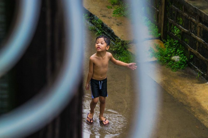 Rain Rainy Days Singing Singing And Dancing Dancing In The Rain Little Boy Childhood Child Typhoon Philippines Manila Water Full Length Spraying Motion Standing Shirtless Wet Smiling Portrait Happiness Swimming Trunks