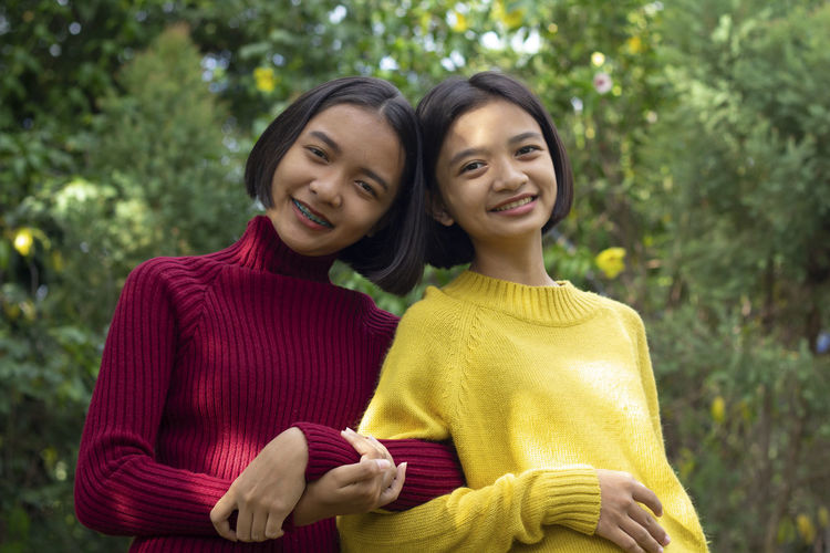 Portrait of smiling teenage girl standing with friend against trees