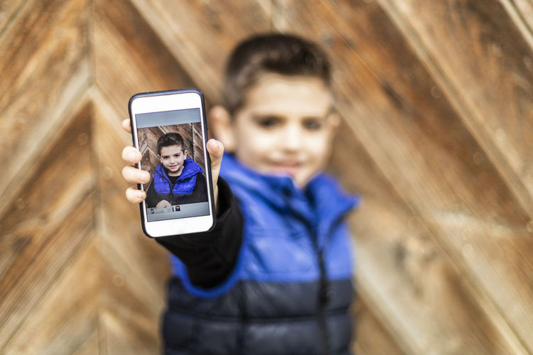 Boy showing mobile phone against closed wooden door