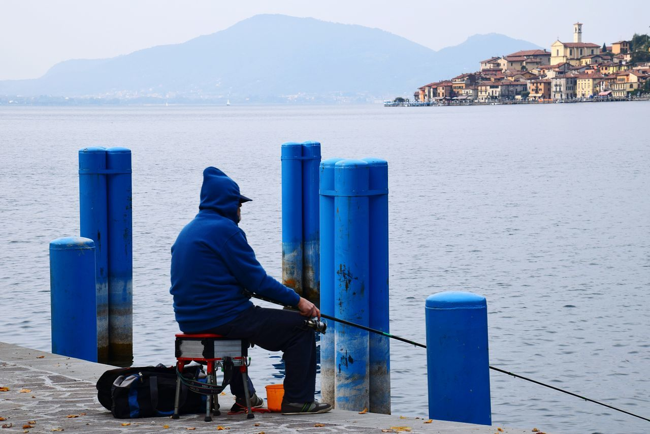 Side View Of Man Fishing On Pier Over Lake