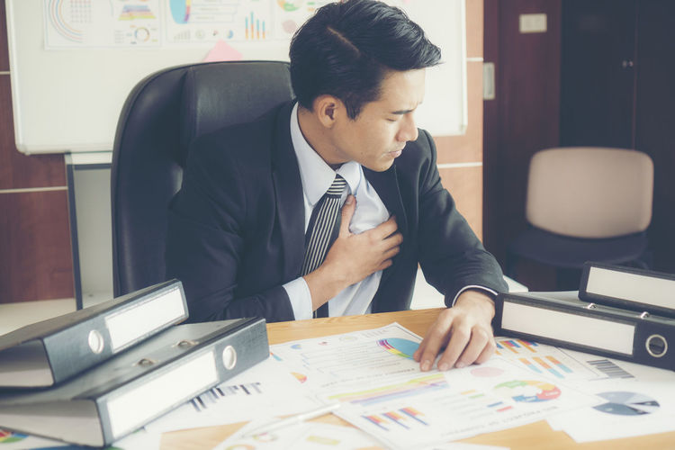 Businessman with heart pain sitting at desk sitting in office