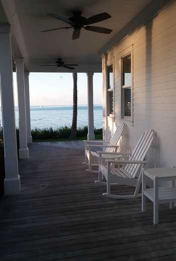 Empty chairs in porch against sea