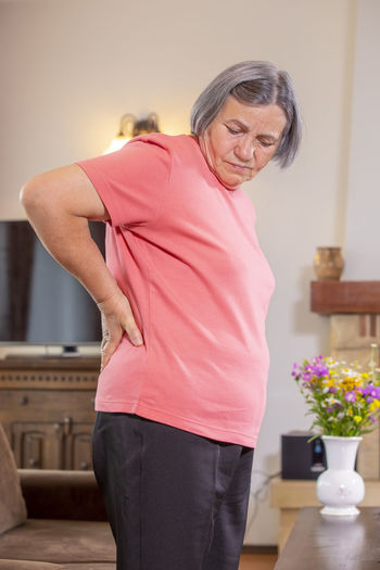 Woman With Backache Standing At Home