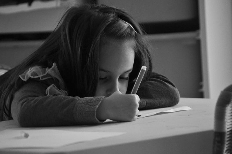 Girl Writing On Paper At Table